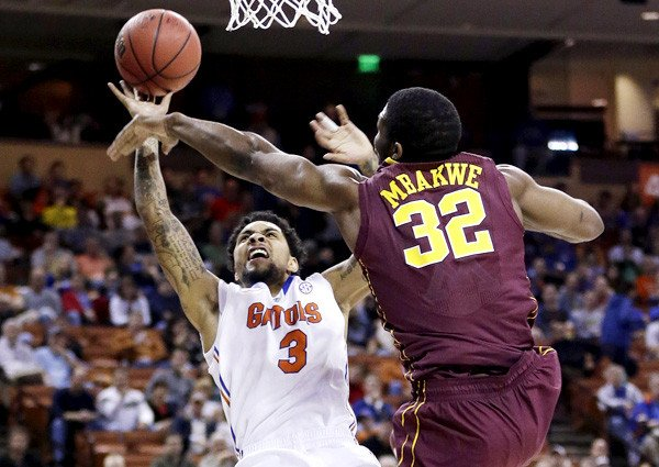 Florida's Mike Rosario #3 is fouled by Minnesota's Trevor Mbakwe #32 on March 24, 2013. (Photo by: Eric Gay/AP)